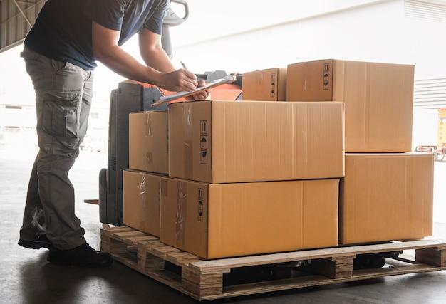 Работник склада, держащий буфер обмена, делает коробки с пакетами управления запасами проверяет коробки отгрузки запасов