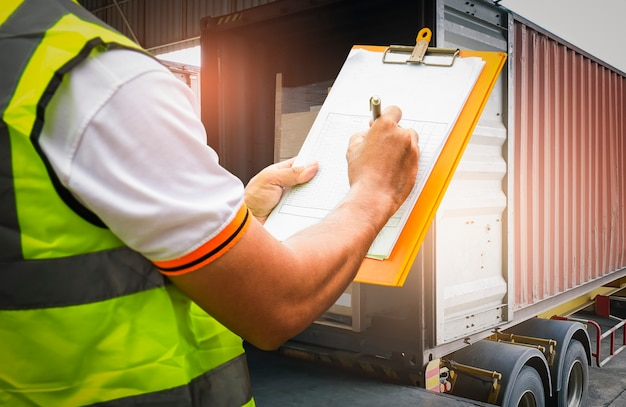 Warehouse worker holding clipboard his control loading cargo boxes into shipping container