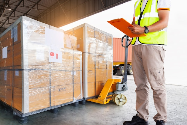 Warehouse worker holding clipboard his control loading cargo pallet into shipping container