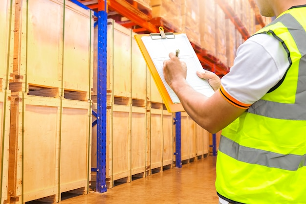 Warehouse worker holding clipboard inspecting products on tall shelves in storage warehouse