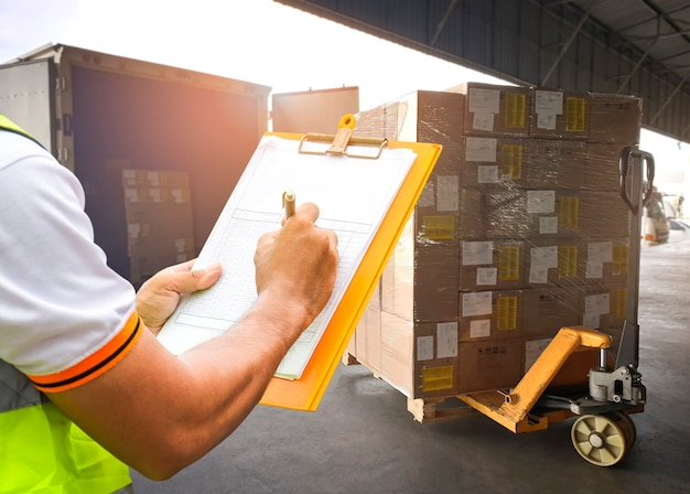 クリップボードを保持している倉庫作業員は、荷物を積み込みますパッケージボックス配達出荷ボックス