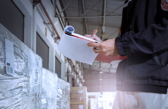 Warehouse worker holding clipboard while checking inventory