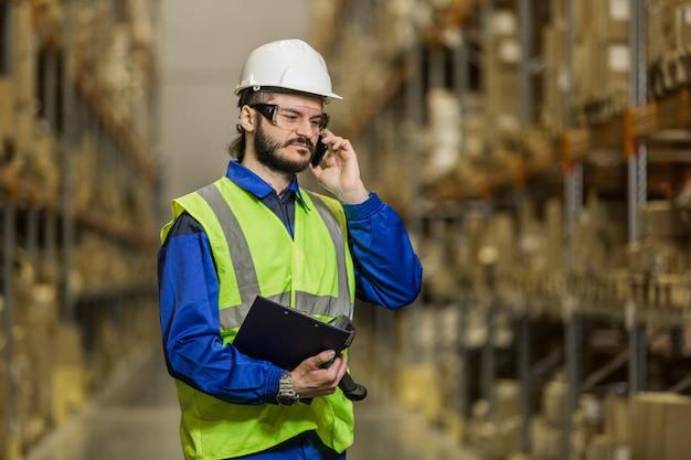 Работник склада в каске и униформе разговаривает по мобильному телефону