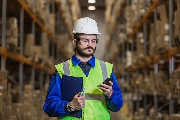 Работник склада в каске с помощью мобильного телефона