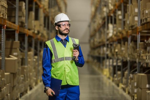 Работник склада в каске со сканером, глядя в камеру