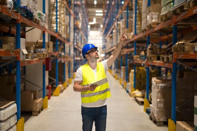 Работник склада в защитной светоотражающей униформе с каской проверяет инвентарь и подсчитывает товар на полке на большом складе