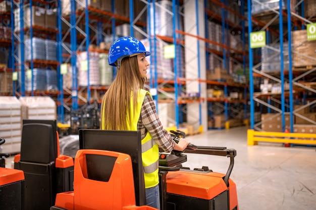 보호 작업복의 창고 작업자가 지게차를 운전하고 저장 시설에서 물품을 조작합니다.