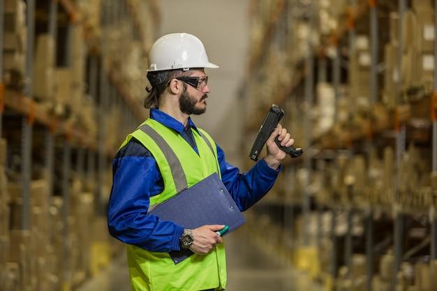 Работник склада в униформе, глядя на сканер
