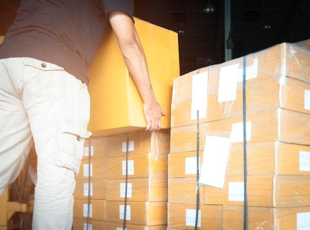 Складской рабочий поднимает отгрузочные ящики на производственном складе.