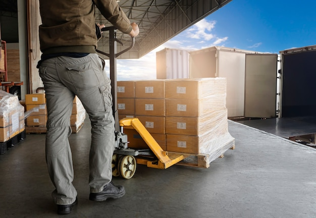 Warehouse worker loading package boxes into shipping container truck