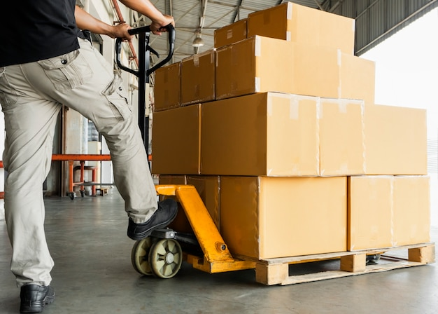 Warehouse worker loading shipment boxes on pallet.