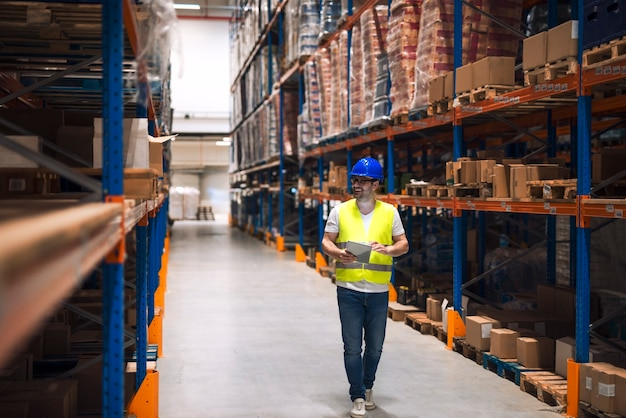Warehouse worker looking at shelves with packages and walking through large warehouse storage distribution area