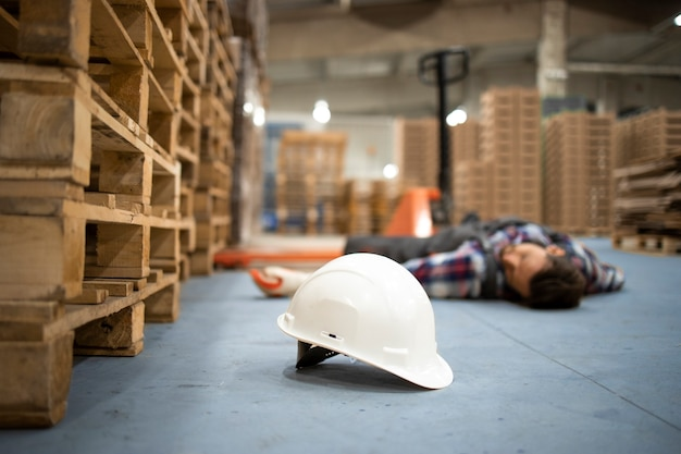 Warehouse worker lying unconscious on the concrete floor after the fall