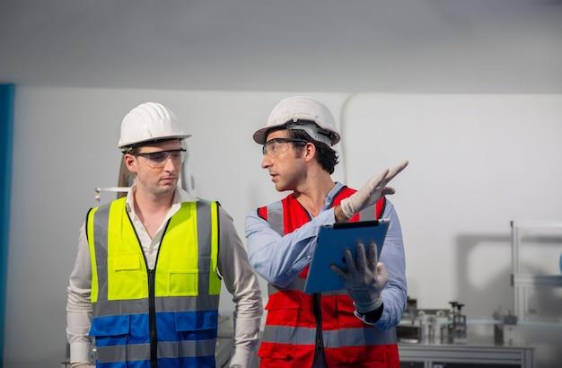 Работник склада в защитной каске проверяет детали заказа с помощью цифрового планшета в инвентарной комнате