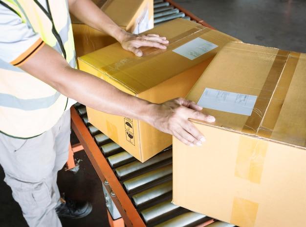 Работник склада перемещает упаковочные коробки на ленточном конвейере распределение складских отгрузочных коробок