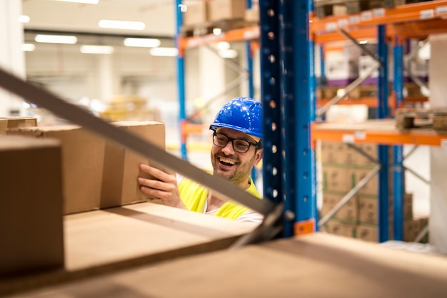 Warehouse worker picking up boxes in large warehouse distribution center.