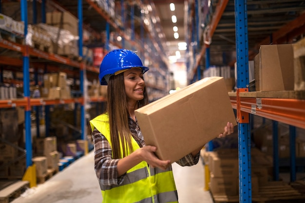 Warehouse worker placing cardboard boxes on the shelf in big warehouse storage area