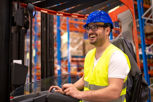 Warehouse worker in protective work wear driving forklift and manipulating goods in storage facility