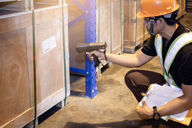 Warehouse worker scanning bar code scanner with package boxes warehouse inventory mangement