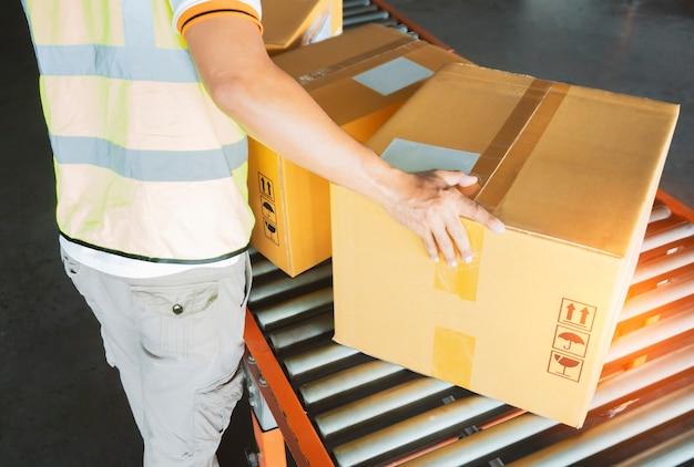 Работник склада, сортирующий упаковочные коробки на ленточном конвейере, складская логистика