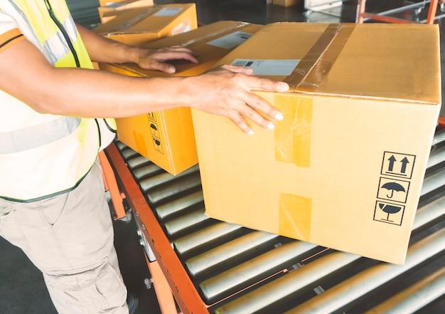Warehouse worker sorting package boxes on rollers conveyor belt