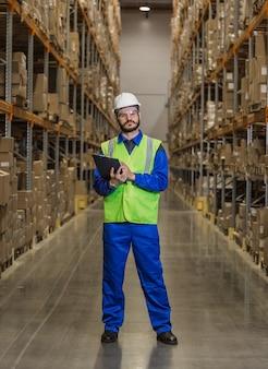 Работник склада, стоящий между рядами с товарами и смотрящий в камеру