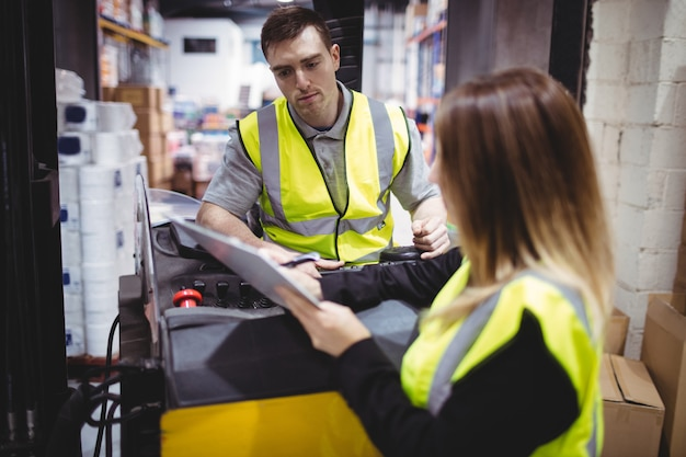 Warehouse worker talking with forklift driver in warehouse