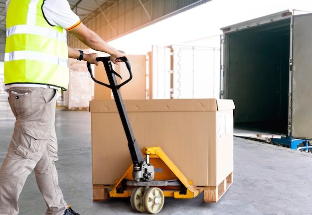 Работник склада разгружает большую партию товара на поддоне в грузовик.
