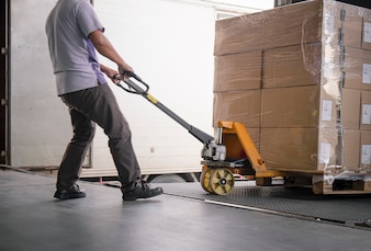 Warehouse worker unloading cargo boxes on pallet. cargo truck parked loading at dock warehouse. Premium Photo