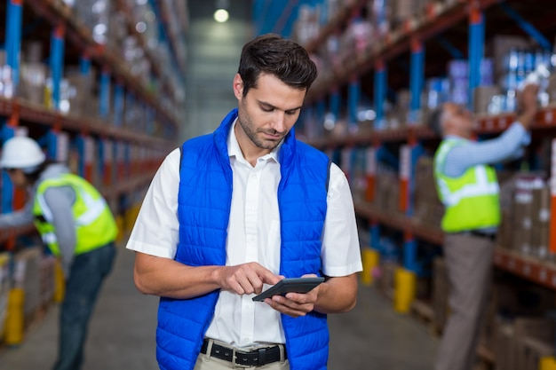 Warehouse worker using calculator