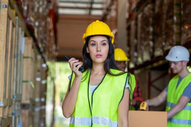 Работник склада с помощью портативного радиоприемника для связи на большом складе.