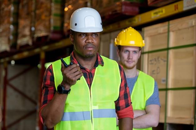 大規模な倉庫での通信にハンドヘルドラジオ受信機を使用する倉庫作業員。