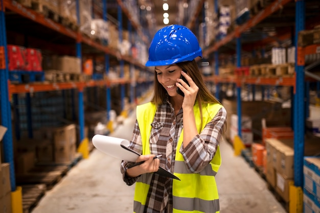 Warehouse worker with hardhat having conversation on the phone and holding checklist in distribution warehouse facility