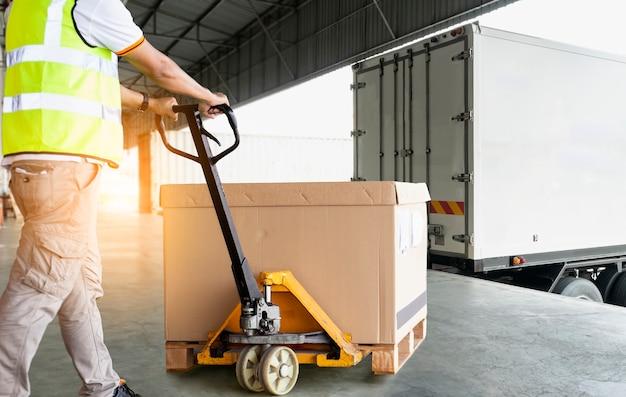 Работник склада, работающий с ручной тележкой для поддонов, загружает поддон тяжелого груза на складе.