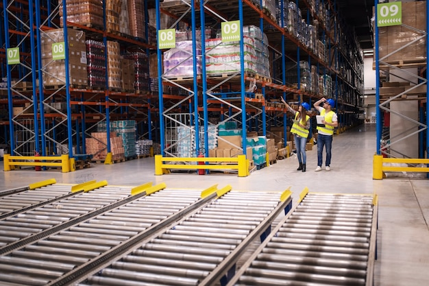 Warehouse workers checking inventory and goods distribution in large storehouse