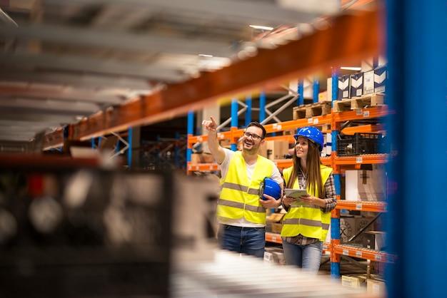 Работники склада, проверяющие инвентарь в большом распределительном складе