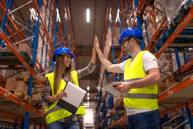 Warehouse workers clapping hands together