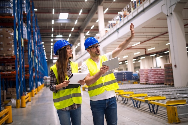 Warehouse workers consulting each other in large factory storage area