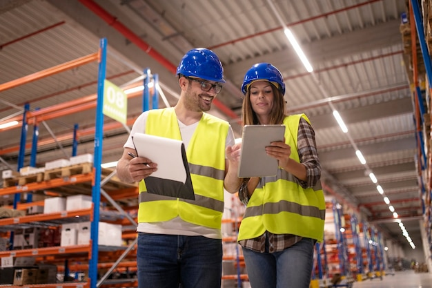 Warehouse workers controlling distribution on tablet in large warehouse storage area
