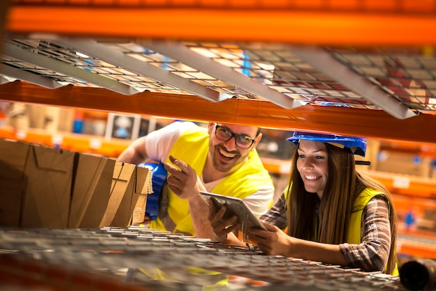 Warehouse workers counting boxes on shelves in large distribution warehouse