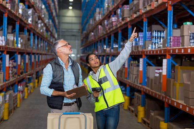 Рабочие склада обсуждают с буфером обмена во время работы