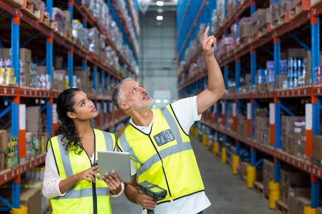 Работники склада обсуждают с цифровым планшетом