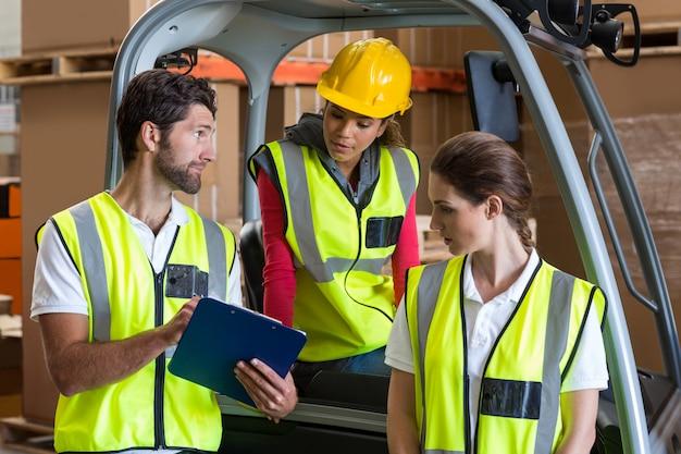 Работники склада разговаривают с водителем погрузчика
