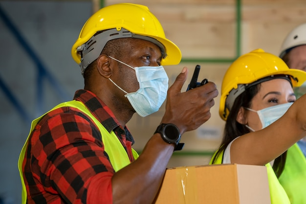 Warehouse workers wearing protective mask  working at warehouse,they work in industry manufacturing factory.