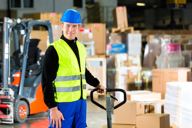 Warehouseman in protective vest pulls a mover with packages and boxes at warehouse of freight forwarding company a forklift