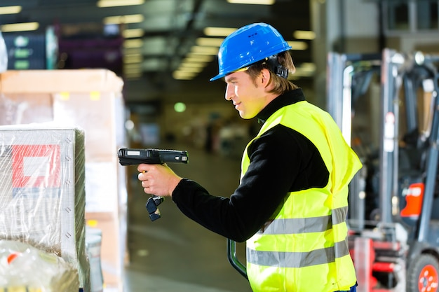 Warehouseman in protective vest using a scanner, standing beside packages and boxes at warehouse of freight forwarding company a forklift