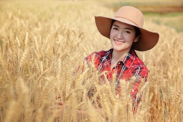 Фермер молодой женщины waring красный цвет рубашки scoth при шляпа сидя в обрабатываемой земле золотого ячменя и очень счастливая с урожайностью на chiangmai таиланде.
