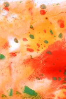 暖かい抽象的な背景赤、黄色、オレンジ色のインクスポットは白い紙に緑の滴とswith