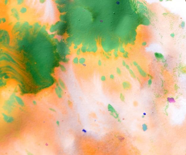 温かみのある抽象的な背景赤、黄、オレンジのインクスポットと緑の滴