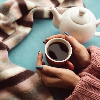 따뜻하고 편안한 컨셉. 여자는 감기 또는 독감을 치료하기 위해 추운 가을 날에 뜨거운 차를 마신다